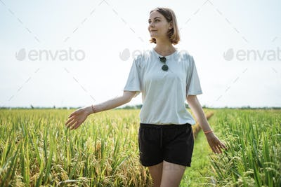 Female walking in the middle of the rice field