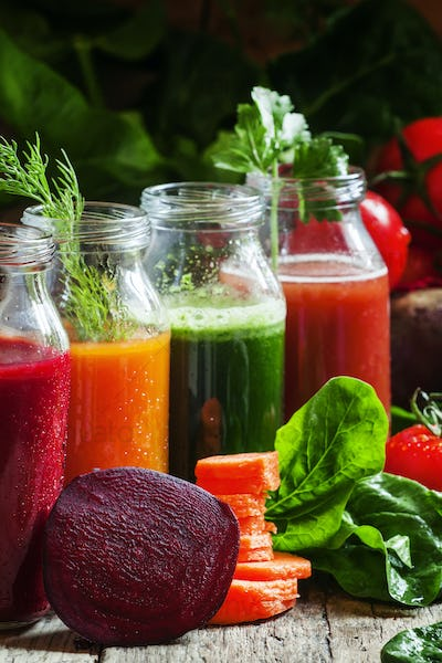 Four kind of vegetable juices: red, burgundy, orange, green, in small glass bottles