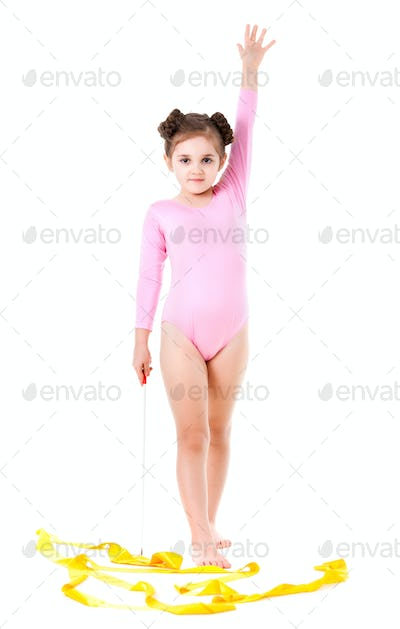 Small positive girl in pink gymnastic jumpsuit standing and holding yellow tape in hand over white