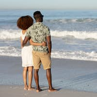 A mixed race couple admiring the view and holding each other on beach