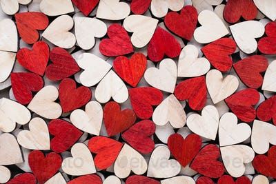 Valentines day background with white end red hearts on wooden background.
