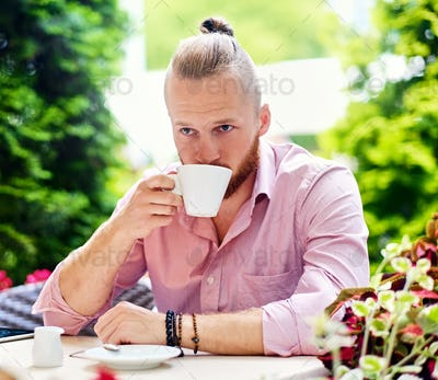 A redhead male dressed in a pink shirt, drinks coffee in an open air cafe.