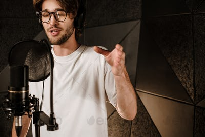 Portrait of young male musician in headphones sensually singing recording song in modern studio