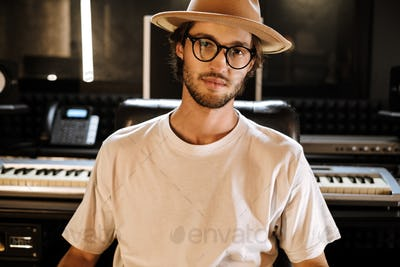 Young stylish sound producer confidently looking in camera working in recording studio