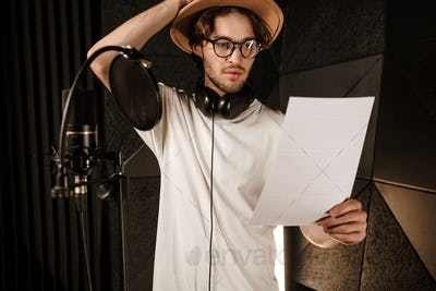 Young thoughtful male singer intently reading text of new song in sound recording studio