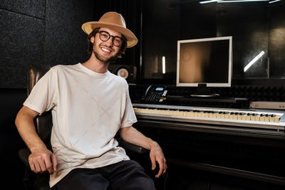 Handsome cheerful guy happily looking in camera in modern sound recording studio