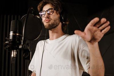 Portrait of young singer in headphones singing during record new song in studio