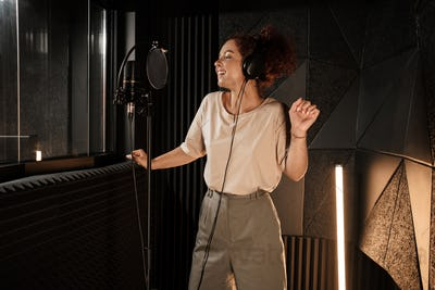 Charming female musician in headphones dreamily dancing while recording song in modern sound studio