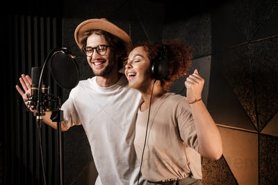 Young attractive musicians happily singing together recording new song in sound studio