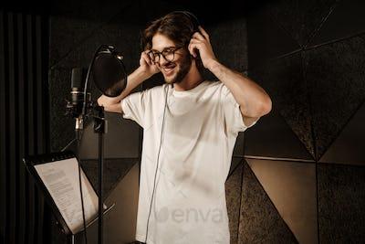Attractive smiling guy happily wearing headphones recording new song in modern studio