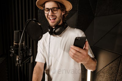 Young attractive male singer with smartphone emotionally singing in recording studio