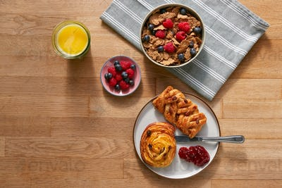 Overhead Flat Lay Shot Of Table Laid For Breakfast With Cereal Pastries And Coffee
