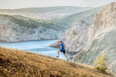 middle-aged man running uphill on trail
