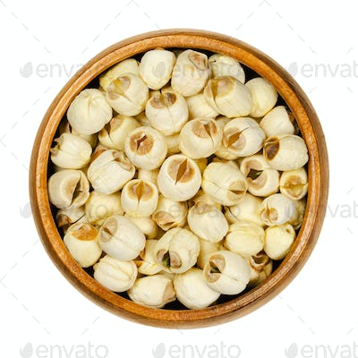 Dried shelled white lotus nuts, water lily seeds in wooden bowl