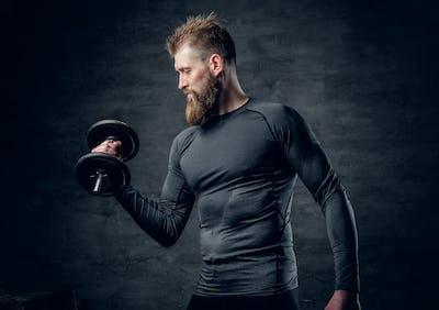 Sporty bearded male holds dumbbell.