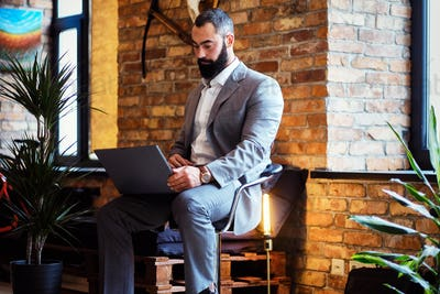 Stylish bearded male works with a laptop.