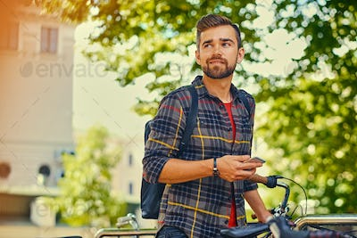 A man using a smart phone near bicycle parking.