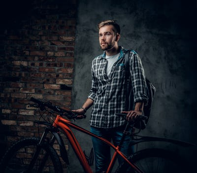 A mant holds red mountain bicycle.