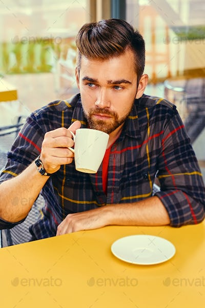A man drinks coffee in a cafe.