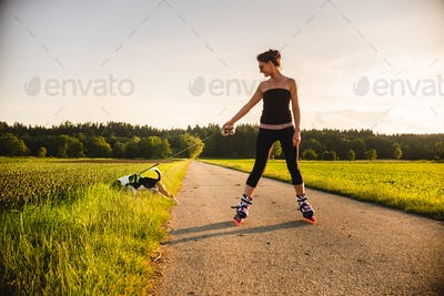 Girl skating with Beagle dog outdoors in nature.