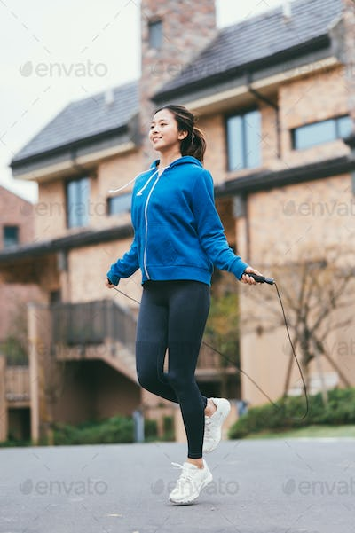 Young Asian woman skipping rope in community