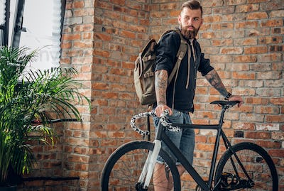 A man holds urban backpack in a room with single speed bicycle.