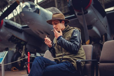A man in a hat smoking cigarette.
