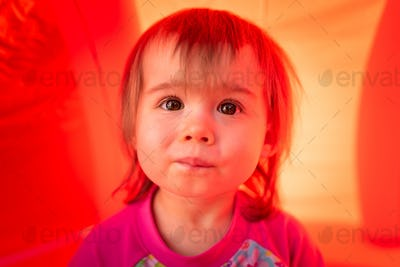 Cute baby girl with big brown eyes outdoors portrait