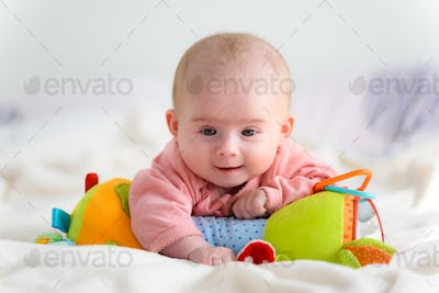 Cute baby girl on bed looking down ad laughing.