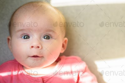 Cute baby girl portrait on a bed on left in pink body suit with big eyes looking at camera.