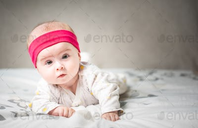 Adorable 6 months old Baby girl infant on a bed on her belly with head up looking into camera with
