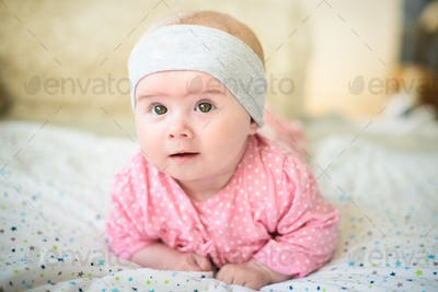 Cute 6 months old Baby girl infant on a bed on her belly with head up looking into camera with her