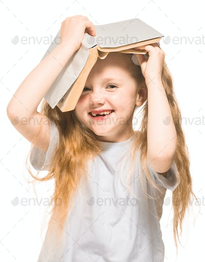 Little girl with red hair with a book on a white isolated background
