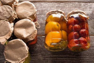 Top View of Homemade Tasty Canned Red And Yellow Tomatoes Near Jars on Wooden Table