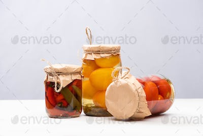 Homemade Delicious Pickled Tomatoes And Chili Peppers in Jars Isolated on Grey