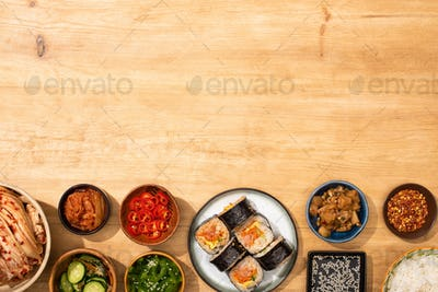 Top View of Bowls With Korean Side Dishes Near Korean Gimbap on Wooden Surface