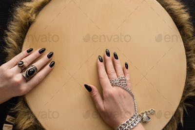 Top View of Shaman With Jewelry Accessories on Hands Playing on Tambourine Isolated on Black