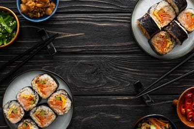 Top View of Chopsticks Near Plates With Tasty Gimbap And Korean Side Dishes on Wooden Surface