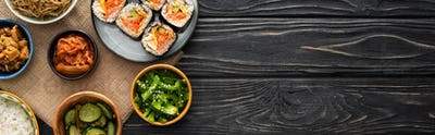 Panoramic Shot of Tasty Korean Side Dishes Near Rice Rolls on Wooden Surface