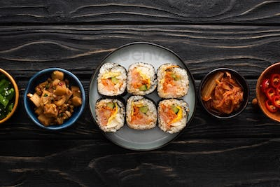 Top View of Plate With Gimbap Near Side Dishes in Bowls on Wooden Surface