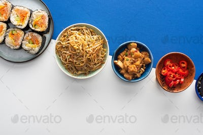 Top View of Plate With Gimbap Near Korean Side Dishes on White And Blue