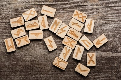 Top View of Signs on Runes on Wooden Background