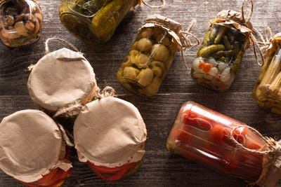 Top View of Homemade Delicious Pickles in Jars on Wooden Table
