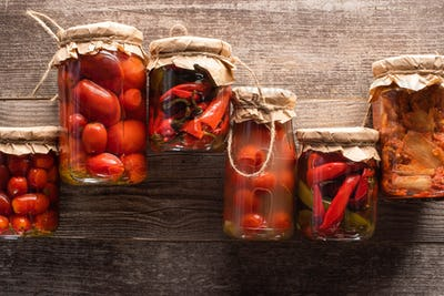 Top View of Red Homemade Tasty Pickles in Jars on Wooden Table