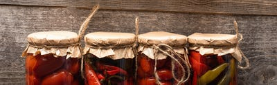 Top View of Tasty Red Homemade Pickles in Jars on Wooden Rustic Table, Panoramic Shot