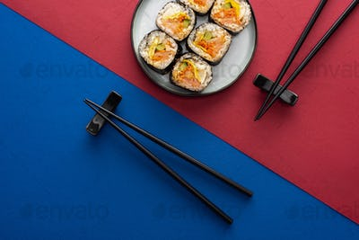 Top View of Chopsticks Near Plate With Delicious Gimbap on Crimson And Blue