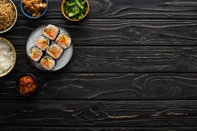 Top View of Bowls With Korean Side Dishes Near Gimbap on Wooden Surface