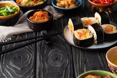 Selective Focus of Delicious Gimbap Near Korean Side Dishes And Cotton Napkin on Wooden Surface