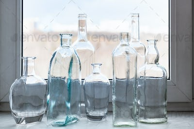 many clear bottles on windowsill and view of park