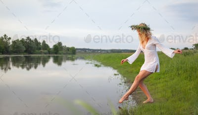 Young sexy beautiful blond woman in white mini dress and floral wreath standing and trying water on